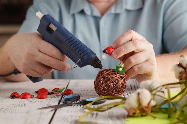 Las manos masculinas hacen una decoración hecha a mano con pegamento