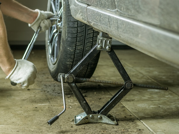 Manos masculinas hicieron girar la rueda del coche en el garaje.