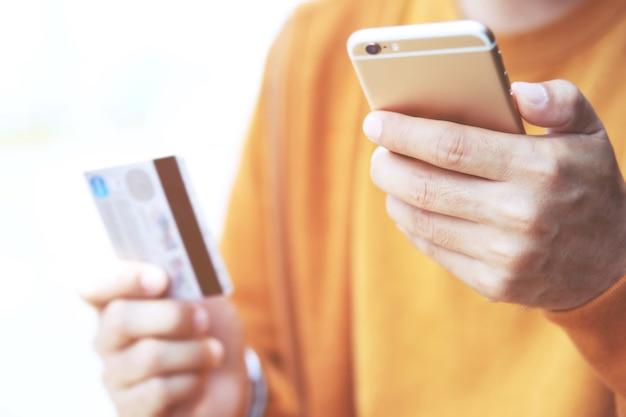 Manos masculinas jóvenes que sostienen la tarjeta de crédito y que usan productos de pedido de asiento de teléfono