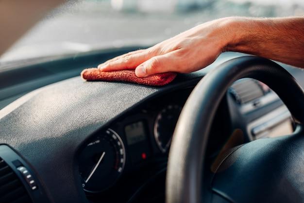 Manos masculinas limpia auto, pulido del salpicadero del coche