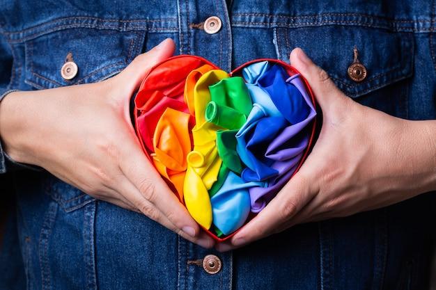 Manos masculinas con el mes del orgullo de la bandera lgbtq del arco iris en forma de corazón