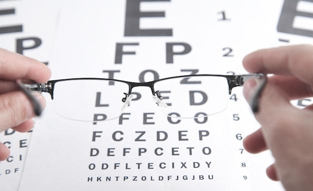 Manos masculinas mostrando anteojos. gráfico de prueba ocular.