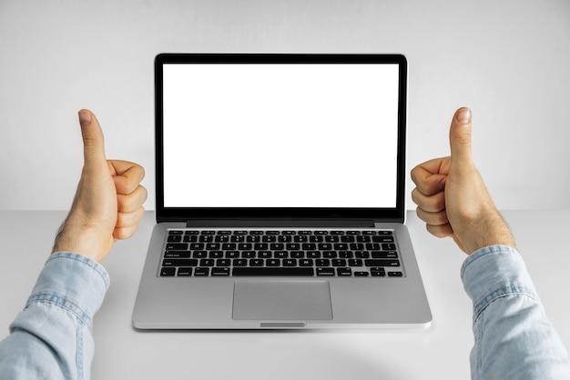 Manos masculinas mostrando los pulgares hacia arriba y computadora portátil con pantalla en blanco en blanco