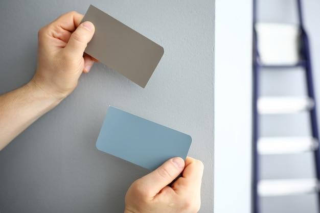 Manos masculinas con muestras de papel de nuevo color de pared
