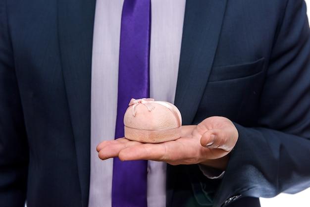 Manos masculinas ofreciendo caja de regalo con anillo de oro en el interior