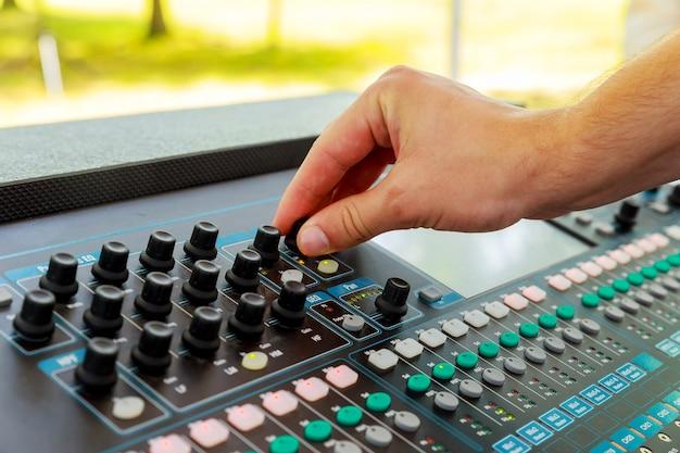 Manos masculinas operando pequeña consola de sonido.