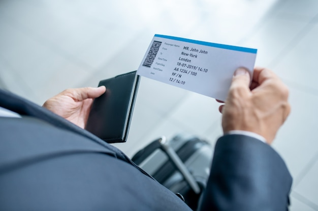 Manos masculinas con pasaporte y boleto de avión