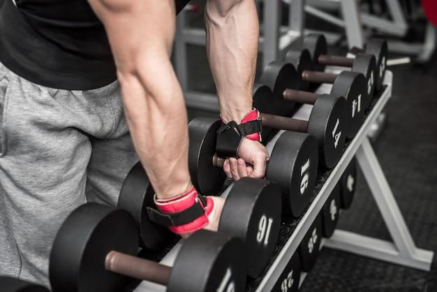 Manos masculinas con pesas en primer plano de gimnasio
