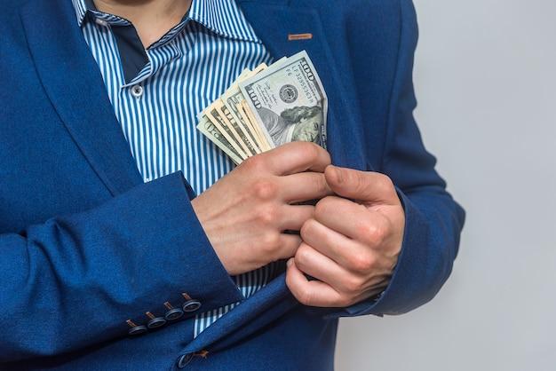 Manos masculinas poniendo billetes de dólar en el bolsillo