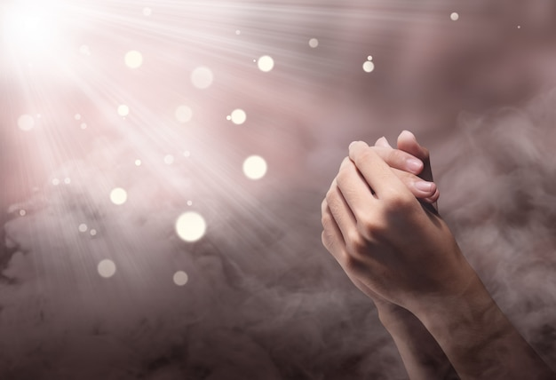 Manos masculinas en posición de oración con ray