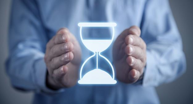 Manos masculinas protegen el icono de reloj de arena. gestión del tiempo