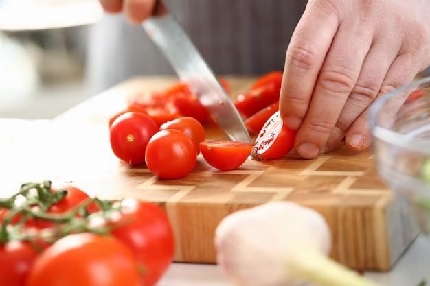 Manos masculinas que cortan el ingrediente maduro del tomate de cereza