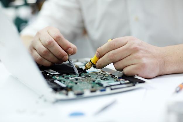 Manos masculinas que reparan la computadora portátil