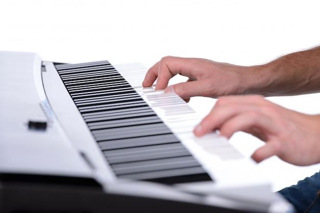 Manos masculinas que tocan el piano digital en blanco.