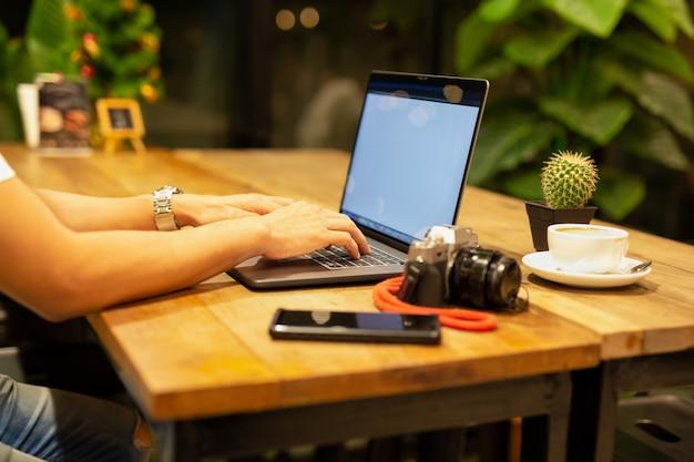 Manos masculinas que trabajan en el ordenador portátil con la cámara y el café en la tabla.