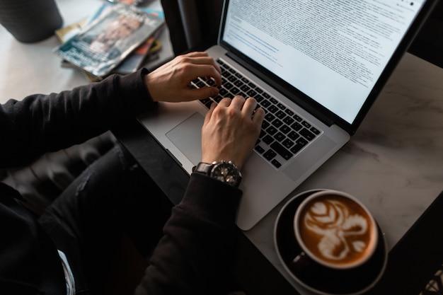 Manos masculinas con relojes de lujo están escribiendo texto en una computadora portátil en un café. chico programador profesional trabaja y bebe café