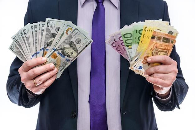 Manos masculinas sosteniendo billetes de dólar y euro en ventilador