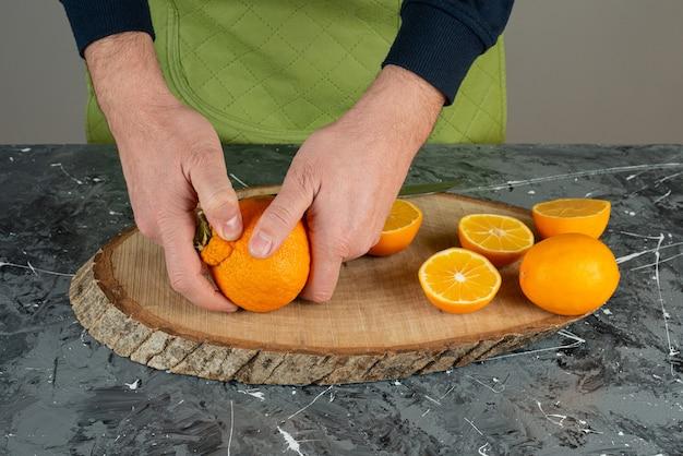 Manos masculinas sosteniendo jugosa mandarina en mesa de mármol.