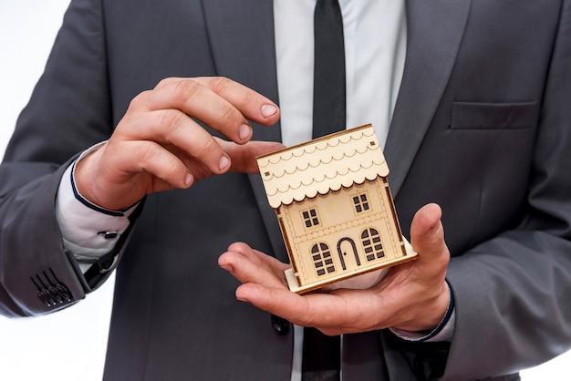 Manos masculinas sosteniendo el modelo de casa de madera de cerca