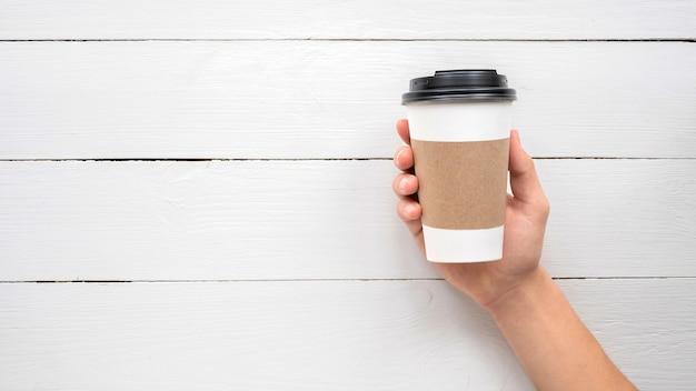 Manos masculinas sosteniendo una taza de café reciclable. idea de reciclaje