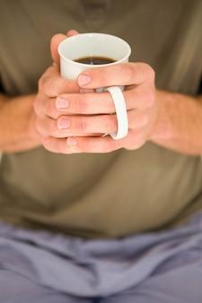 Manos masculinas sosteniendo una taza de té en el dormitorio