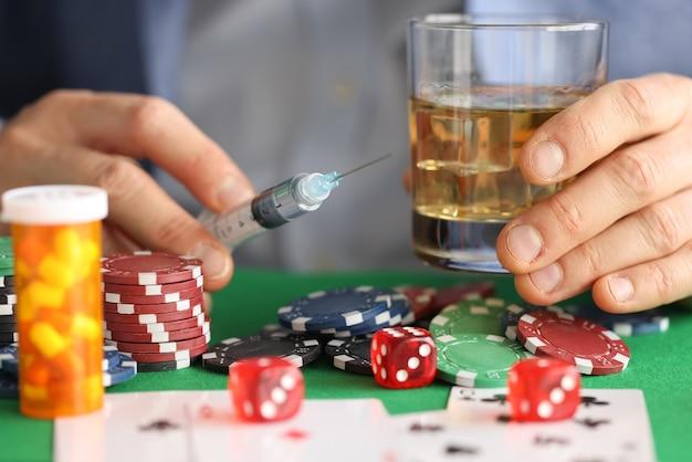 Las manos masculinas sostienen la jeringa con aguja y vaso con alcohol junto a fichas de casino