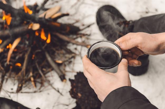 Manos masculinas sostienen una taza de café cerca de una fogata ardiente.