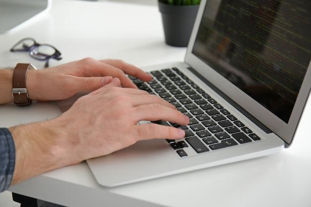Manos masculinas en el teclado de la computadora portátil, primer plano