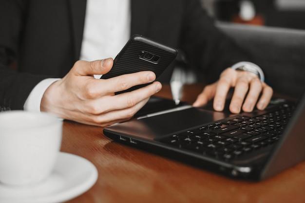 Manos masculinas con un teléfono inteligente y una computadora portátil en una cafetería con un café en el escritorio.