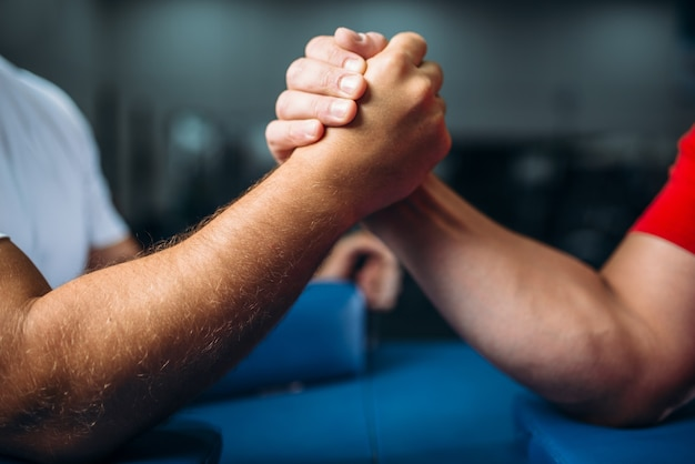 Manos masculinas unidas en la mesa, concepto de lucha libre