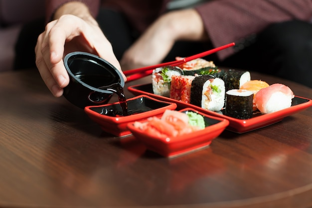 Manos masculinas vierte salsa en un plato. set de sushi