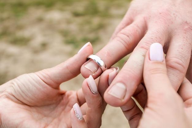 Manos matrimoniales con anillos la novia pone el anillo en el dedo del novio