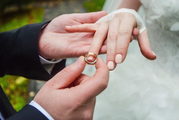 Manos de matrimonio con anillos. birde lleva el anillo en el dedo del novio
