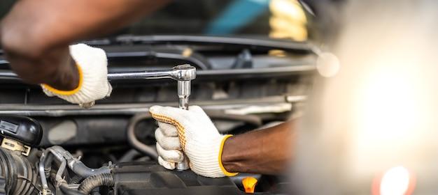 Manos mecánico de automóviles de experiencia en el servicio de reparación de automóviles. concepto de garaje de mantenimiento y servicio automático de automóviles.