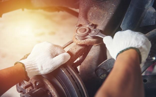 Manos de mecánico de automóviles en servicio de reparación de automóviles.
