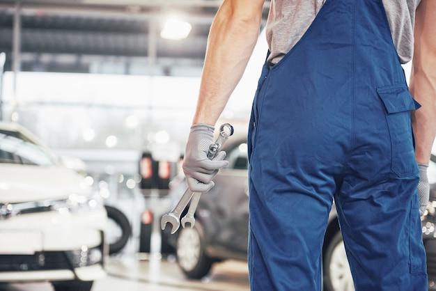 Manos de mecánico con llave en garaje