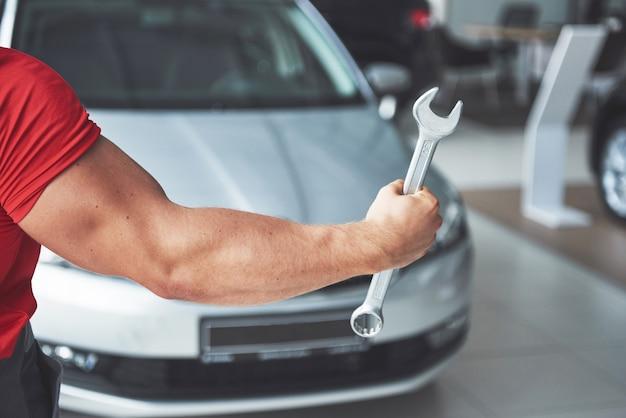 Manos de mecánico con llave en garaje.