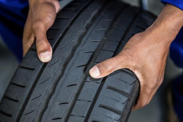 Manos de mecánico con los neumáticos