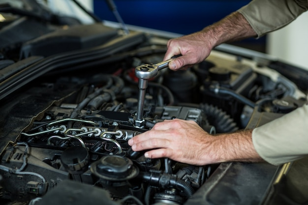 Manos de mecánico de servicios de un coche