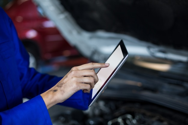 Manos de mecánico de sexo femenino que usa la tableta digital
