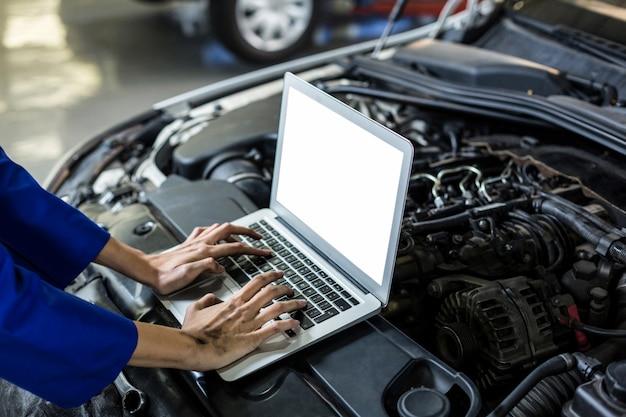 Manos de mecánico de sexo femenino usando la computadora portátil