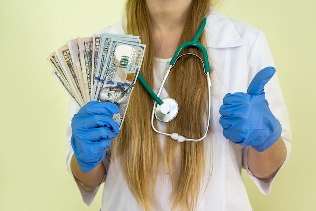 Manos del médico contando dólares aislados en un verde
