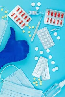 Las manos del médico en guantes azules. medicina para el coronavirus. medicamentos en la lucha contra covid-19. píldoras, jeringas, termómetro, máscara médica en mesa azul.