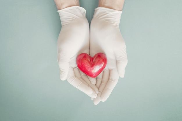 Manos del médico con guantes con corazón rojo, seguro médico, concepto de donación