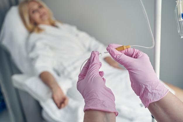 Manos de médico profesional haciendo juego con tubos de plástico transparente antes de colocar un gotero con vitaminas