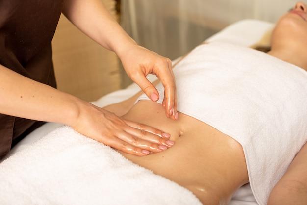 Manos del médico que realiza la palpación abdominal del paciente que sufre de dolor