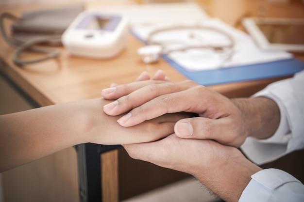 Las manos del médico que sostienen la mano del paciente femenino para tranquilizarlo con un estímulo amistoso, empatía por apoyo