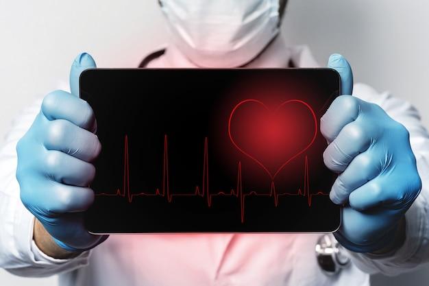 Manos del médico con tablet pc que muestra el ritmo cardíaco en la pantalla