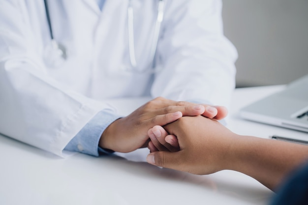Las manos del médico varón sosteniendo la mano del paciente masculino para aliento y empatía. tranquilizador y apoyo. animación y apoyo del paciente