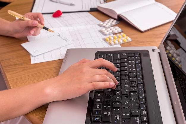 Manos de los médicos escribiendo en la computadora portátil y prescripción de llenado